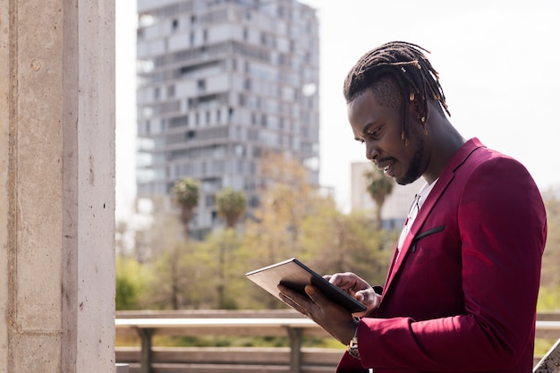 도시에서 야외에서 태블릿을 사용하는 흑인 사업가