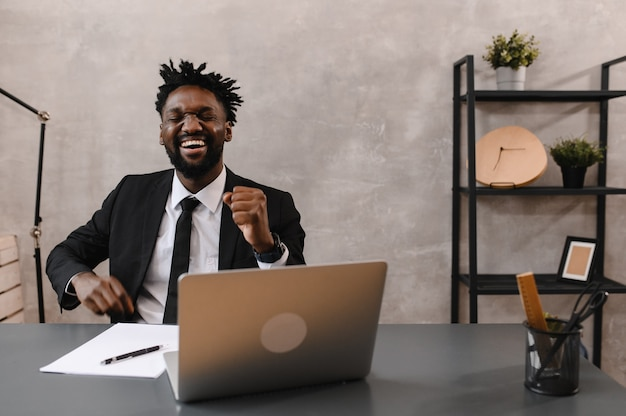 Black businessman using laptop for analyzing data stock market