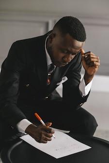 データ株式市場、外国為替取引グラフ、オンライン証券取引所取引を分析するためにラップトップを使用している黒人実業家