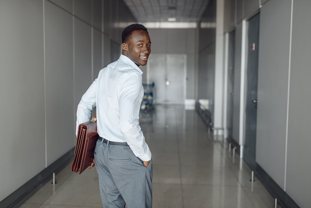 Black businessman with briefcase in office hall. successful business person walking down the corridor, black man in formal wear