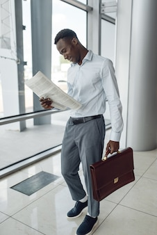 新聞、モールを読んでブリーフケースを持つ黒人実業家。成功したビジネスパーソン、フォーマルウェアの黒人男性、ショッピングセンター