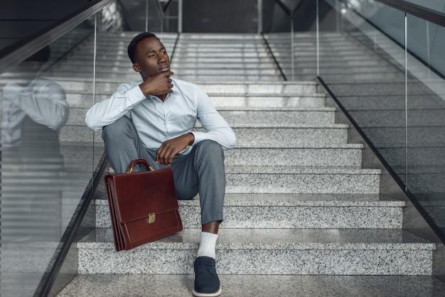 계단에 앉아 서류 가방으로 흑인 사업가