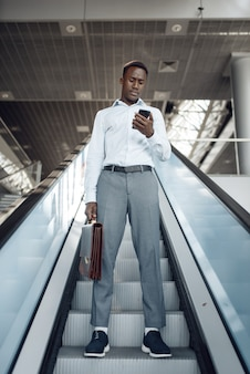 Black businessman with briefcase talking by phone on the escalator in mall. successful business person, black man in formal wear, shopping center