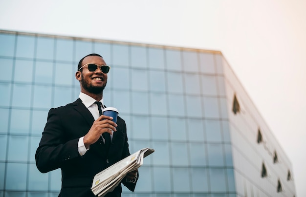 Black businessman with coffee in his hand smiles as he reading the newspaper in front of the skyscraper.