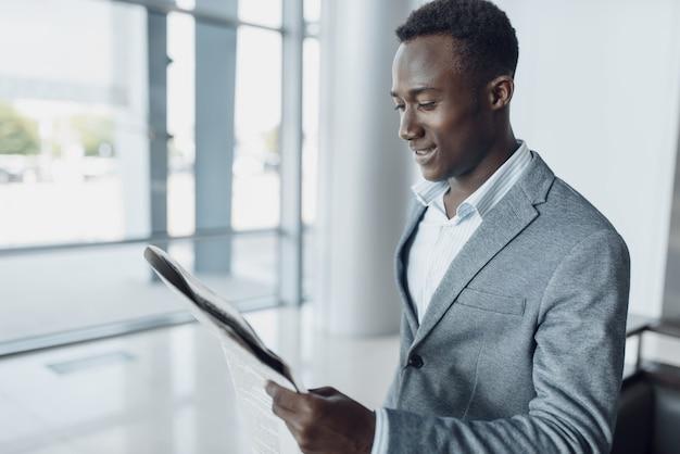 オフィスビルで新聞を持つ黒人実業家。成功したビジネスパーソン、フォーマルウェアの黒人男性