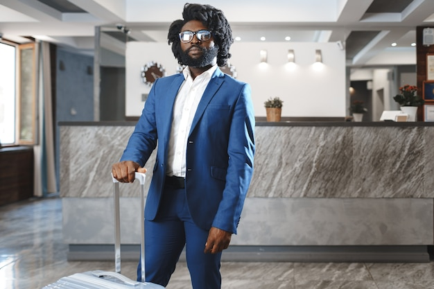 Black businessman with packed luggage standing in hotel lobby close up
