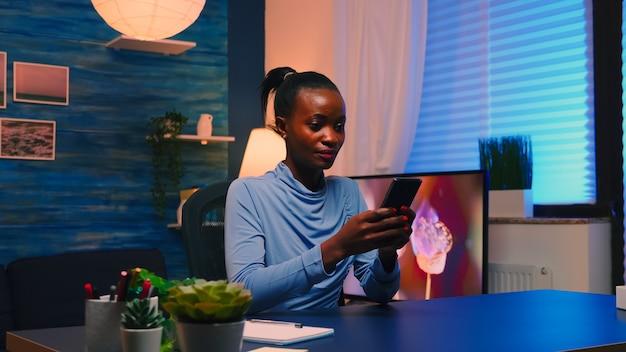 열심히 일한 후 휴식을 취하는 거실 사무실에 앉아 스마트폰을 사용하여 탐색하는 흑인 여성 사업가. 아프리카 원격 직원이 팀과 채팅하는 데 기한을 준수하여 초과 근무합니다.