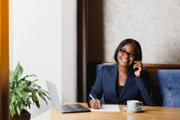 Черный бизнесвумен с помощью планшетного компьютера в кафе