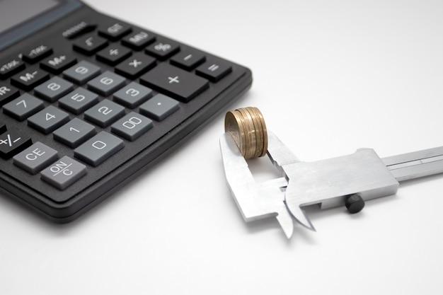 キャリパーの黒い電卓とコイン。ビジネスと金融。