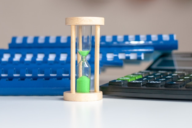 Black calculator and hourglass with green sand close-up stand on a white wooden table, business environment of the workplace