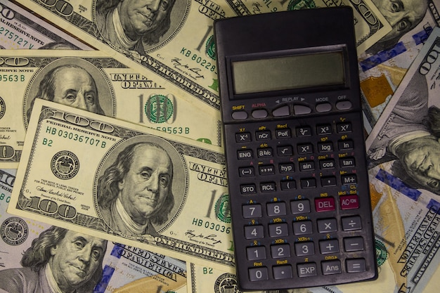 Черный калькулятор на фоне американских стодолларовых купюр