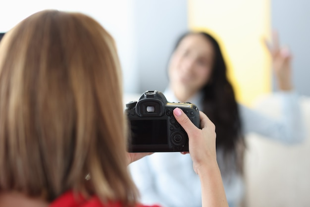 Black camera in hands of woman photographer with woman model in photo studio. home photo session of friends tfc concept.