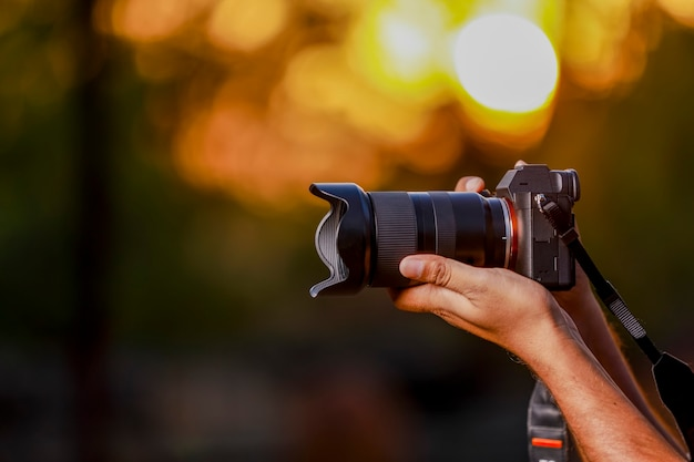Black camera held by photographer's hand with sunset
