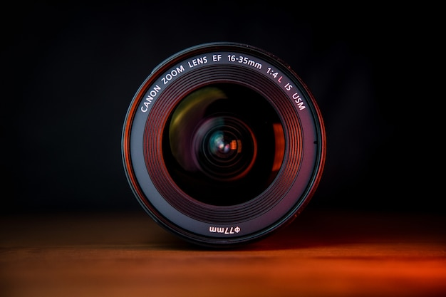 茶色の木製テーブルに黒いカメラレンズ