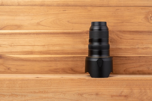 Black camera lens placed upside down on wooden floor.