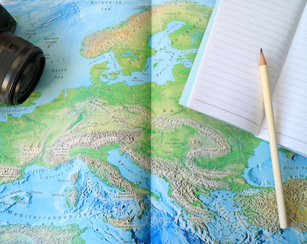 Black camera and lined notebook with white pencil on the world map