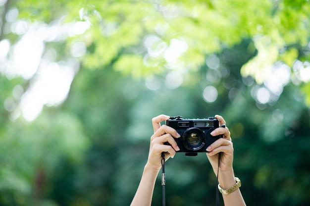 Black camera and natural green background