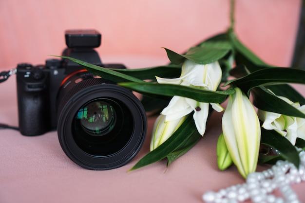 Черная камера с объективом и белыми лилиями и ожерельем из жемчуга на розовом фоне. выборочный фокус. нет видимых логотипов и брендов