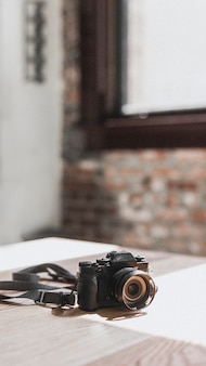 Black camera on a wooden table mobile phone wallpaper