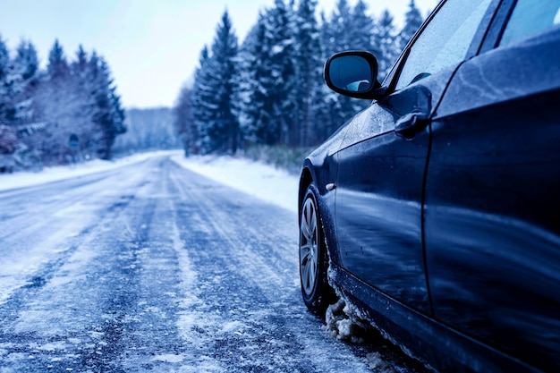 Black car on an iced road surrounded by trees covered with snow