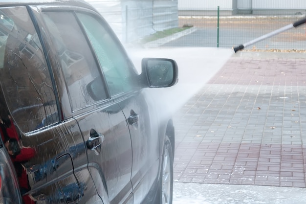 Черная машина моется сильной струей воды на автомойке самообслуживания