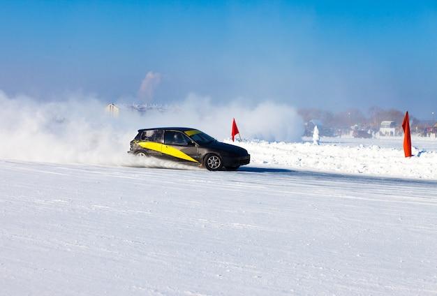 Black car moving on ice making lots of ice splashes