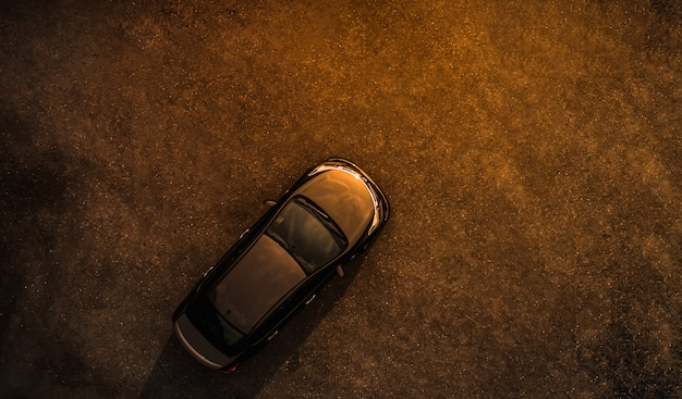Black car on parking lot concrete evening time aerial view