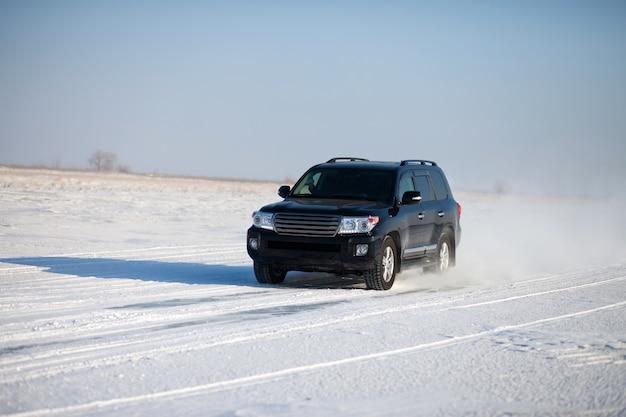 Черная машина едет по снегу