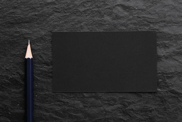 어두운 돌 배경에 검정 카드와 연필