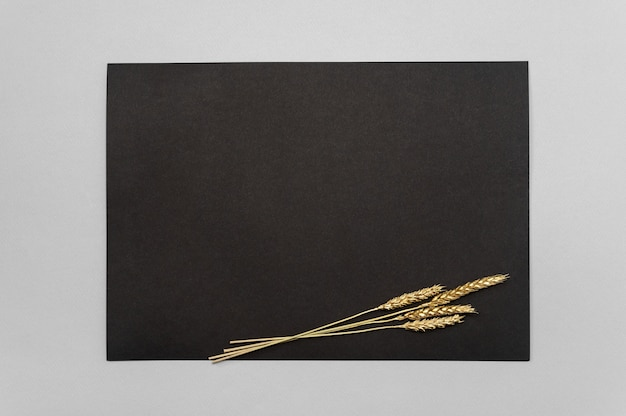 Black card with golden dried grass decoration on neutral table. black pape