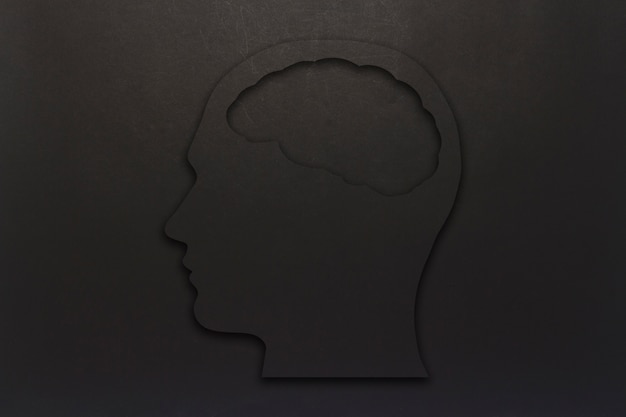 Black cardboard head with a brain on a black background. copy space. flat lay, top view.