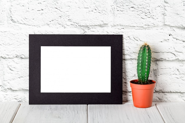 Black cardboard photo frame on white table against brick wall. mockup against brick wall. mockup