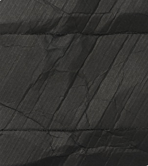 Black cardboard texture with folds, full frame, inside of perfume box, close up
