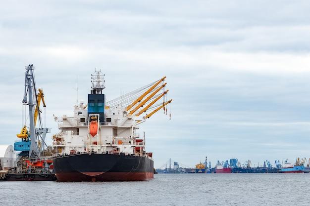 ヨーロッパのリガ港に積み込まれる黒い貨物船