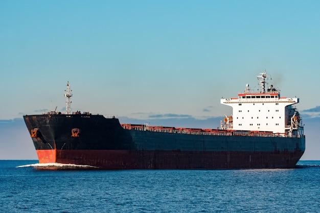 Черный грузовой корабль движется в спокойной воде балтийского моря. рига, европа