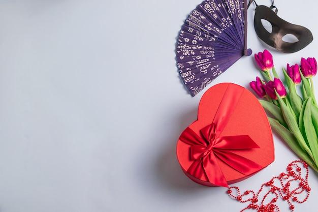 黒いカーニバルマスク、トーンの弓とハートの形の赤いギフトボックス、新鮮な紫色のチューリップの花束、ビンテージファンとビーズ