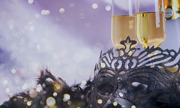 Black carnival mask with glittering and champagne glasses