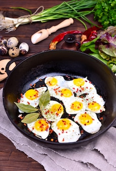 Black cast-iron frying pan with fried quail eggs