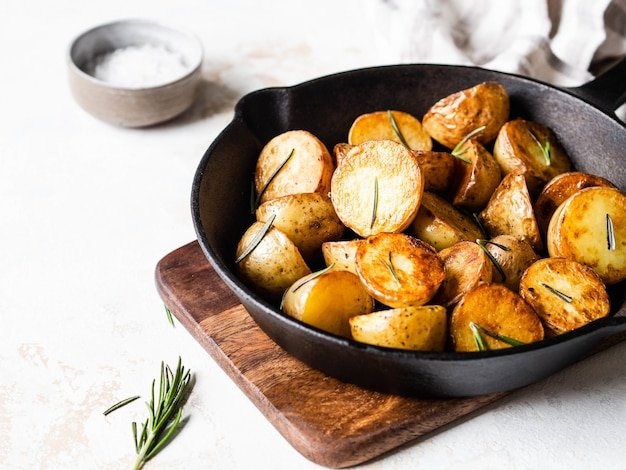 Black cast iron pan with fried roasted potato wedges with herbs on a light surface
