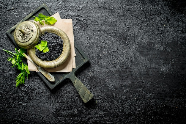 Black caviar in a bowl on a cutting board with parsley. on black rustic surface
