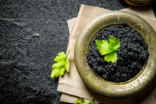 Black caviar in a bowl on paper with parsley. on black rustic table