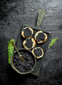 Black caviar in a bowl and sandwiches with caviar on a cutting board with dill. on black rustic surface