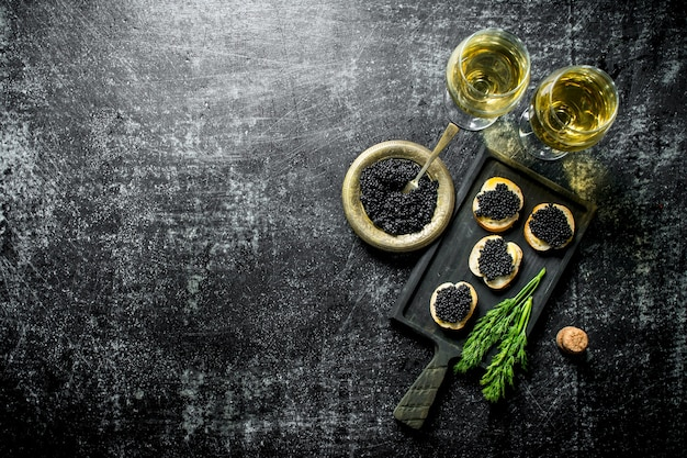 Black caviar in a bowl and sandwiches with caviar on a cutting board with dill and white wine. on black rustic surface