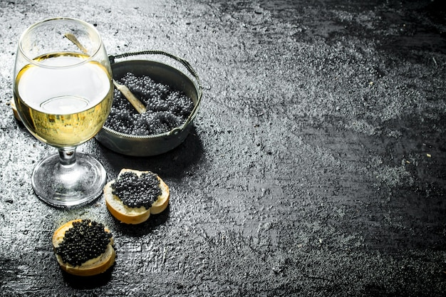 Black caviar in a bowl with sandwiches and wine. on black rustic table