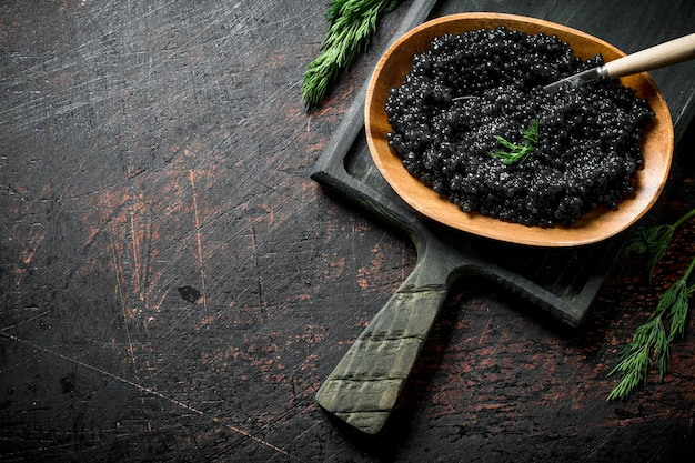 Black caviar in a bowl with a spoon on the cutting board. on dark rustic
