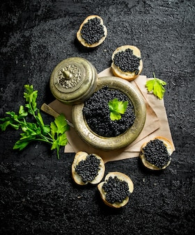 Black caviar on bread slices and caviar in a bowl on paper with parsley. on black rustic surface