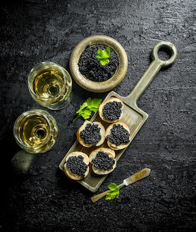 Black caviar on bread slices and the wine. on black rustic