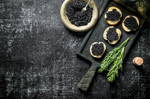 Black caviar on bread slices with dill. on black rustic table