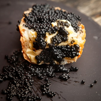 Black caviar high angle view on a bread and dark background