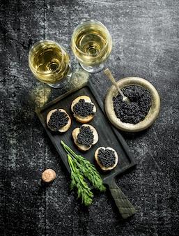 Черная икра в миске и бутерброды с икрой на разделочной доске с укропом и белым вином. на черном деревенском фоне